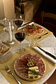 A table laid with an antipasto platter, red wine and bruschetta