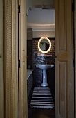 Open door with a view into a bathroom with a white pedestal sink with a lighted mirror