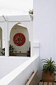 Blick auf orientalische Arkaden und bunte Wandlampe im Gang