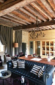 Open living-dining room in a country home with a wooden beam ceiling, striped floor length curtains hanging at the windows