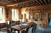 Spacious dining room with a wooden beam ceiling in a country home, long dining table with wicker chairs