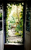 View through an open terrace door of a lush garden