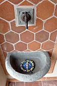 Stone sink and old faucet in front of a wall with terracotta tiles