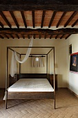 Simple bedroom in a country home with a canopy bed on terracotta flooring and a beam ceiling