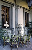 Terrace with rattan furniture and busts on a window ledge in a villa