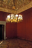 Brass chandeliers in a red anteroom with ceiling frescos and stucco