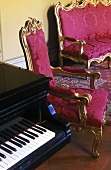 Rococo style furniture -- chair and bench with gilt frame and red upholstery next to a piano