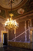 Unrestored anteroom of a castle with ceiling frescoes and a brass chandelier