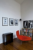 Corner of a living room with a lounger upholstered in red in front of half-high bookshelves and photos on the wall