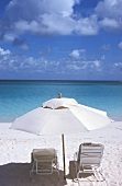 White sand beach, view of the ocean -- lounge chairs under a sun umbrella casting a wide shadow