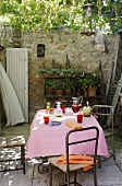 Refreshing drinks on a table with a pink tablecloth and a shelf of flower pots against a high stone wall