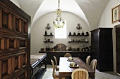 A vaulted ceiling in a dining room with dark wooden furniture
