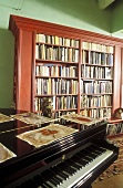 Living room with piano and mahogany bookcase against green wall