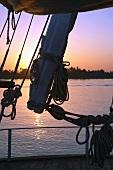 Blick durch Takelage eines Segelbootes auf Abendröte mit Sonnenuntergang, Nil, Ägypten