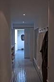 Schmaler Flur mit Einbaustrahler, Garderobe und weisslackiertem Boden