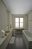 White designer style bathroom with a wide countertop in front of a wall with gray lacquer engineered flooring