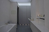 Half-darkened bathroom in designer style -- vanity top with recessed sink and built-in cabinets with plinth lighting