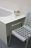 Gray metal chair with holes in the seat and backrest next to a bathtub