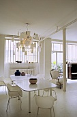 Dining room in a white loft -- white table with chairs and ceiling lamp with sheets of memo pad paper