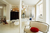White loft with antique upholstered sofa and red pillow in front of a column and dining area