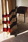 Floor length curtain with red stripes and stool on a terracotta floor
