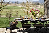 A table laid on a terrace with a bunch of tulips and view over the Mediterranean landscape