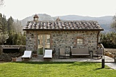 Renovated stone building with elegant patio furniture and a well manicured lawn