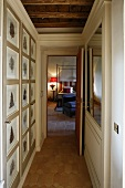 Narrow hallway with a picture gallery and open door with a view of a canopy bed