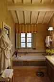Vor Fenster eingebaute Badewanne mit gemusterten Fliesen und Holzdecke im Dachraum