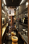 Wine store with black wooden shelves and wine bottles on display and stools shaped like corks