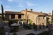 Blue sky above a Mediterranean villa with a natural stone facade and terrace