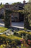 View across the professionally designed garden of a Mediterranean villa with a natural stone facade