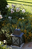 Floor lamp at the edge of a path in front of blooming yellow flowers in the garden