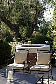 Elegant patio chairs upholstered in bright fabric in front of a circular grill