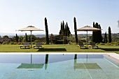 Relaxing hours, poolside, with lounge chairs under a sun umbrella and a view of the Mediterranean countryside