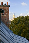 View across a roof and a brick chimney of a gold plated church dome