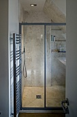 Built in shower under a roof with glass doors and a stainless steel heated towel rail