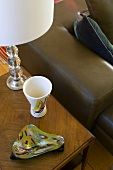 Ash tray, drinking vessel and a table lamp on a wooden side table