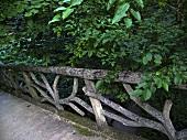 Rustikales Holzgeländer einer Brücke und Bäume