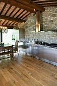 Stainless steel kitchen in front of a natural stone wall and beam ceiling in a renovated country home