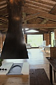 Open fireplace with a black flue under the wooden beam ceiling of a renovated country home