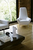 White armchair in the corner of a living room in front of floor to ceiling windows on a wooden floor