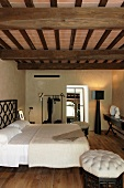 An elegant bedroom beneath a rustic wooden beam ceiling in a renovated country home