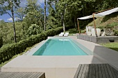 Turquoise water in a pool edged with stone in a garden and a covered wooden deck with patio furniture