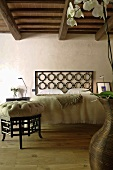 Renovated country home with rustic wooden beam ceiling - Asian style foot stool and bed with a headboard made of decorative metal grillwork