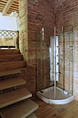 Glass shower stall in the corner of a room made of brick and wooden stairs