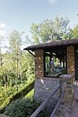 Renoviertes Landhaus mit Ziegelfassade und raumhohen Fenstern am Hang