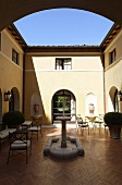 The sunny Mediterranean courtyard of a villa with a stone fountain
