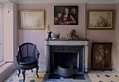Sitting room with a fireplace in an old building with paintings on a pink wall and patterned floor tile