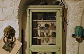 Grüner Vitrinenschrank mit Antiquitäten vor rustikaler Wand